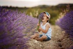 有一个帽子的可爱的逗人喜爱的男孩在淡紫色领域 库存照片