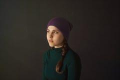 有一个帽子的少妇在黑暗的背景 库存图片