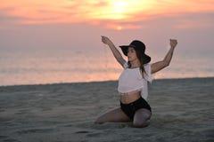 有一个帽子的年轻典雅的俏丽的夫人在户外海滩黎明背景,画象 免版税库存图片