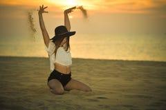 有一个帽子的年轻典雅的俏丽的夫人在户外海滩黎明背景,画象 免版税库存照片