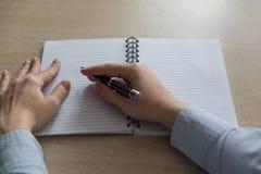 有一个干净的笔记本桌的顶视图 妇女的手拿着一支笔并且准备写 库存图片