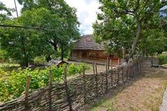 有一个庭院和一个房子的柳条篱芭在它后的一个茅屋顶下 图库摄影