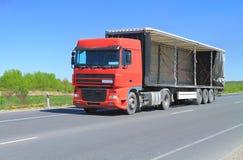 有一个开放拖车遮篷的一辆牵引车拖车卡车 免版税库存照片