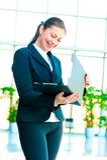 有一个开放文件夹的年轻愉快的女商人在手中 免版税库存图片
