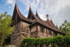 有一个异常的屋顶的木农村房子在米南佳保人的村庄在苏门答腊海岛上的  免版税库存照片
