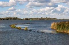 有一个弯曲的防堤的河在延迟阳光下 库存图片
