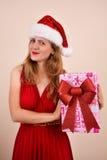 有一个当前箱子的圣诞节肉欲的女孩,穿戴在圣诞老人服装 库存图片
