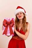 有一个当前箱子的圣诞节肉欲的女孩,穿戴在圣诞老人服装 免版税图库摄影
