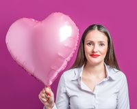 有一个心形的气球的美丽的年轻女人在明亮的背景 华伦泰` s日概念 免版税库存照片