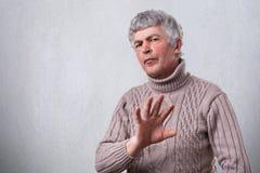 有一个恼怒的皱眉的成熟的人显示消极的表示拒绝与棕榈的标志 消极人的情感面孔表示fe 免版税库存照片