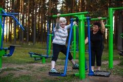 有一个成人女儿的一名年长妇女做着在体育操场的锻炼 库存图片