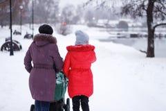 有一个成人女儿的妇女和一辆婴儿推车在冬天停放 库存照片