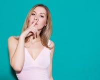 有一个手指的美丽的白肤金发的少妇在显示她的嘴唇保留沈默,静寂 获得一件桃红色的礼服的秀丽女孩乐趣 绿色 免版税库存照片