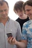 有一个手机的三个人 免版税库存照片