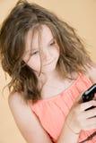 有一个手机的八岁的女孩 免版税图库摄影
