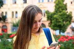 有一个手机的女孩读一则消息, 免版税库存图片