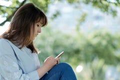 有一个手机的少妇本质上 免版税库存照片