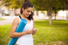 有一个手机的瑜伽女孩 免版税库存照片