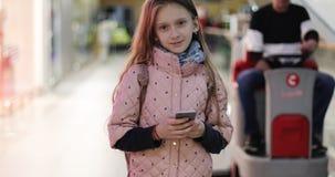 有一个手机的逗人喜爱的女小学生在购物中心站立 影视素材