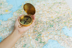 有一个指南针的手在与地图的一张桌上 图库摄影