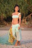有一个捕鱼网的亚裔女孩在海滩 免版税库存照片