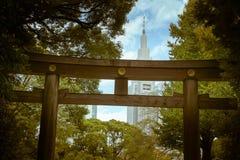有一个摩天大楼的一个torii门在背景中,显示在东京之间传统和现代建筑学的对比  免版税库存照片