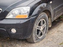 有一个放气的前轮的一辆黑汽车 免版税图库摄影