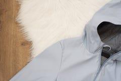 有一个敞篷的妇女蓝色雨夹克在木背景 时尚和设计的概念,购物 图库摄影