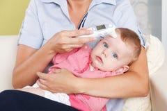 有一个数字体温计的婴孩 库存照片