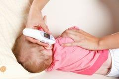 有一个数字体温计的婴孩 免版税库存照片