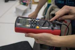 有一个数字式多用电表的妇女在手中 免版税库存图片