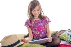 有一个数字式片剂和苹果的女小学生 库存图片