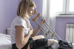 有一个整直法的一年轻女人在她的腿坐床 设法起来与拐杖 手术后期间 图库摄影