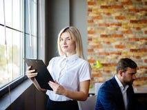 有一个文件夹的年轻女商人在工人的背景 免版税库存照片