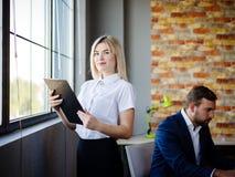 有一个文件夹的年轻女商人在工人的背景 图库摄影