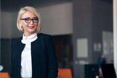 有一个文件夹的愉快的年轻女商人在办公楼 免版税库存图片
