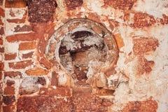 有一个断裂的红砖墙壁以圈子和白色石灰石油灰的形式 库存照片
