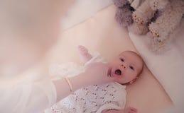 有一个新出生的婴孩的妈妈她的胳膊的 女孩抱着一个婴孩 免版税库存图片