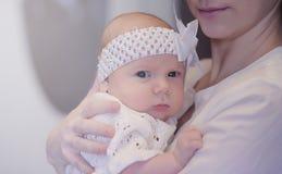有一个新出生的婴孩的妈妈她的胳膊的 女孩抱着一个婴孩 库存照片