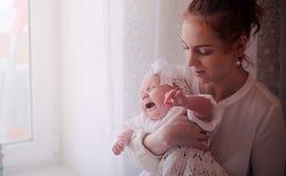 有一个新出生的婴孩的妈妈她的胳膊的 女孩抱着一个婴孩 图库摄影
