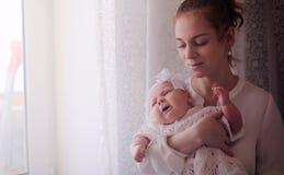 有一个新出生的婴孩的妈妈她的胳膊的 女孩抱着一个婴孩 免版税图库摄影