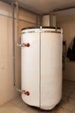 有一个新的现代固体燃料锅炉、加热的电温暖的供水系统和管子的一个国内家庭锅炉室 免版税库存照片