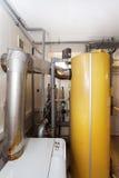有一个新的现代固体燃料锅炉、加热的电温暖的供水系统和管子的一个国内家庭锅炉室 图库摄影