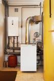 有一个新的现代固体燃料锅炉、加热的电温暖的供水系统和管子的一个国内家庭锅炉室 库存照片