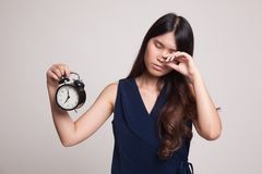 有一个时钟的困年轻亚裔妇女早晨 免版税库存照片