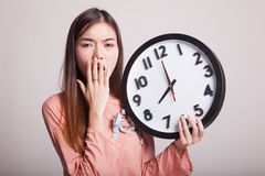 有一个时钟的困年轻亚裔妇女早晨 库存照片
