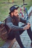 有一个时髦的胡子的一个英俊的行家在他的胳膊的旅客和纹身花刺在便衣和帽子穿戴了有袋子的 库存照片