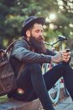 有一个时髦的胡子的一个英俊的行家在他的胳膊的旅客和纹身花刺在便衣和帽子穿戴了有袋子的 免版税库存照片
