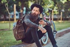 有一个时髦的胡子的一个英俊的行家在他的胳膊的旅客和纹身花刺在便衣和帽子穿戴了有袋子的 免版税图库摄影
