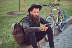有一个时髦的胡子的一个英俊的行家在他的胳膊的旅客和纹身花刺在便衣和帽子穿戴了有袋子的 库存图片